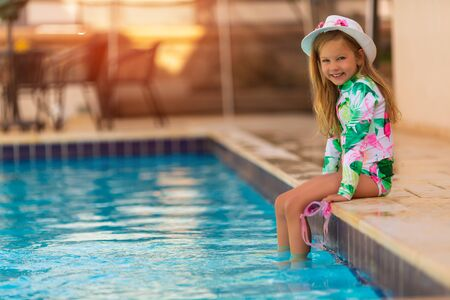Child in swimming pool. Tropical vacation for family with kids. Little girl wearing white swimsuit and sun hat playing in outdoor pool of exotic island resort. Water and swim fun for children 写真素材