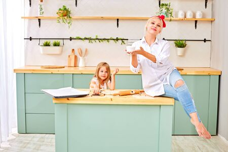 Attractive young woman and her little cute daughter are cooking on kitchen. Having fun together while making cakes and cookies.