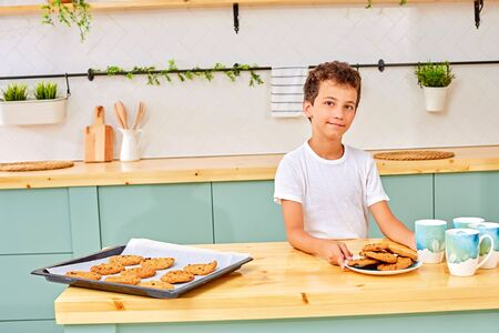 boy eats a sweet, tasty, freshly baked cookie. Son drinks tea in the morning, breakfast in the kitchen at home. Family, food and people concept