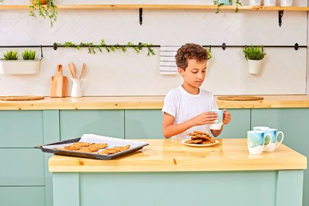 Cute little boy eating cookies and singing tea for breakfast on day off