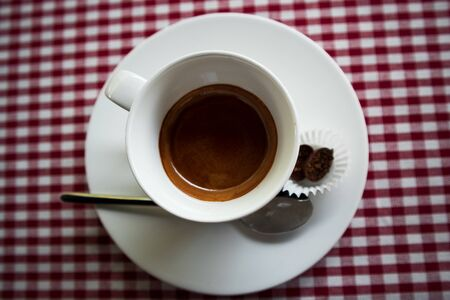 Strong espresso coffee on a checkered background with a metal spoon and chicolad, top view