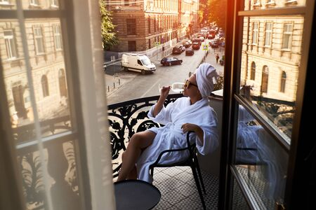 Beautiful blonde in a white coat enjoying a glass of white wine sitting on a hotel terrace against