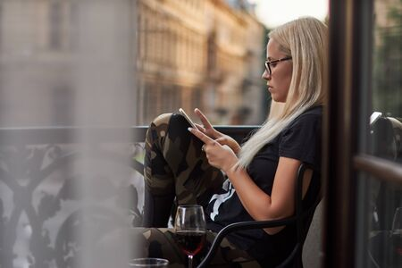 woman drinks red wine, reads social networks, chatting and likes her cell phone 写真素材