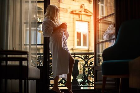 beautiful slender girl with long hair wore in a white bathrobe standing barefoot near a large window
