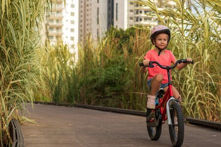 Little girl riding bicycles along a wooden path outside the city wearing helmets as protective equipment