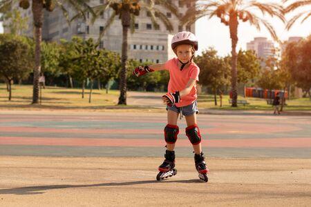 Child on inline skates in park. Kids learn to skate roller blades