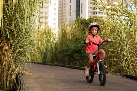 Happy child rides a bike on bike path. Cyclist child girl enjoys good weather and cycling
