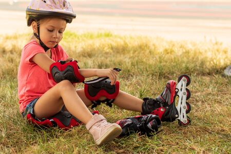 little girl puts on protection for roller skating