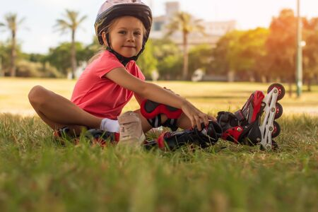 Cute little blonde girl sitting on green grass and putting on roller skates