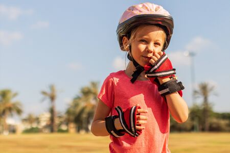 Happy little girl wearing helmet and handguard playing in the park