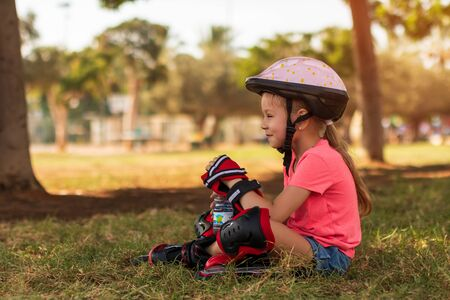 young girl resting after ride on roller skates in the park, holding in hand a bottle with water