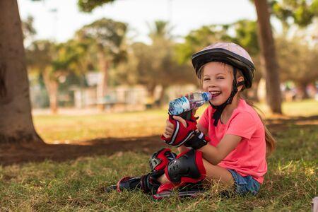 Little girl in roller skates drinking water at park