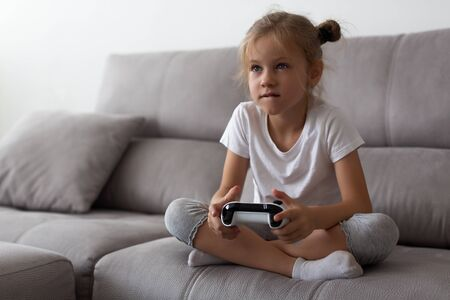 Serious little girl playing video games at home