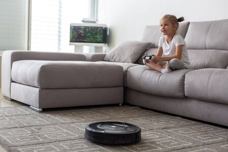 Kid with robot vacuum cleaner playing it at home 스톡 콘텐츠