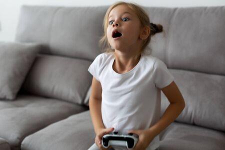 emotional portrait of blonde girl dressed in white. little gamer is sitting on sofa