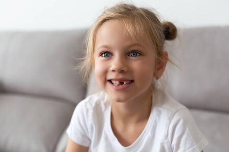 A school-age girl without a front tooth is laughing. Close-up. Change of teeth