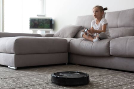 Robotic vacuum cleaning room while girl playing video game