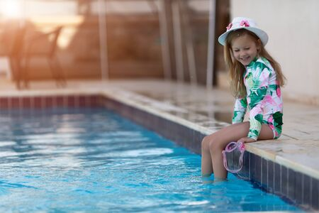 Kid girl with sun protection cream on her skin spends time in the pool. Children, summer, holiday and healthcare concept Stockfoto