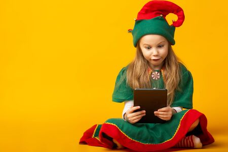 elf sits on the floor checking the list and making sure that they have all the presents Stockfoto