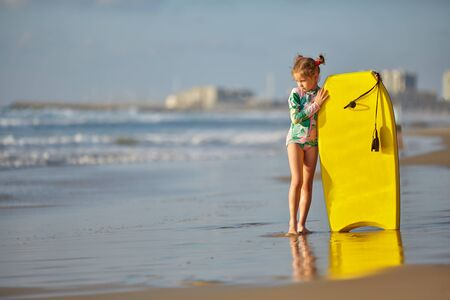Travel Beach Vacation. Close Up Of Healthy Happy Beautiful little girl in a swimsuit With Surfboard