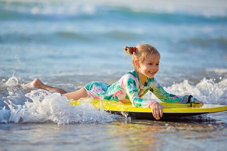 foamy waves of the beautiful autumn sea splashing alongside a charming little girl on a yellow surfboard