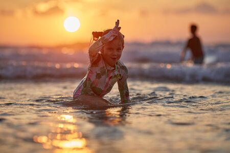 Happy cheerful girl having fun and playing to the sea. Little girl playing on the beach at sunset