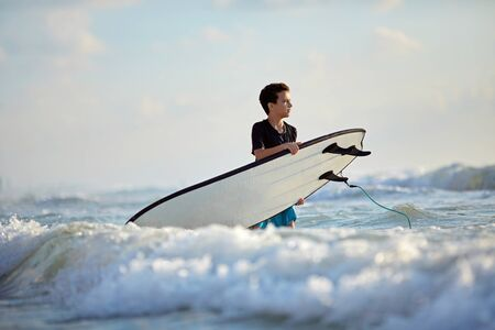 Confident boy knee-deep in water with a surfboard Stockfoto