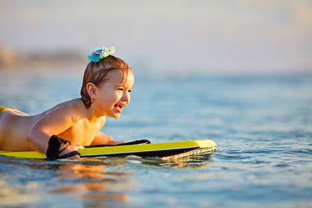 little girl conquers strong waves during golden sunset