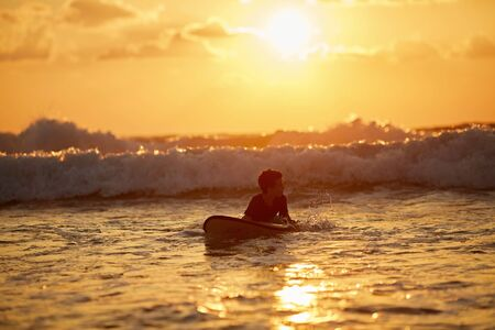 Skilled teenager riding surfboard and balancing along wavy sea at vibrant dusk.