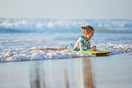 foamy waves of the beautiful autumn sea splashing alongside a charming little girl on surfboard