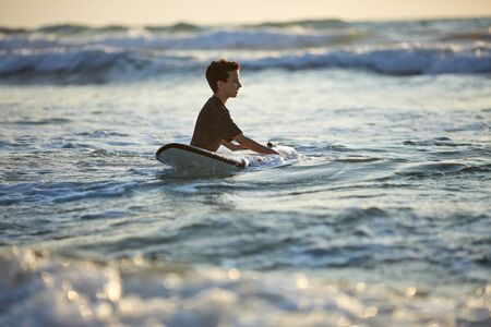Teenager boy surfing on tropical beach in Asia. Child on surf board on ocean wave