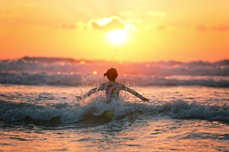 girl at sunset jumping on the waves