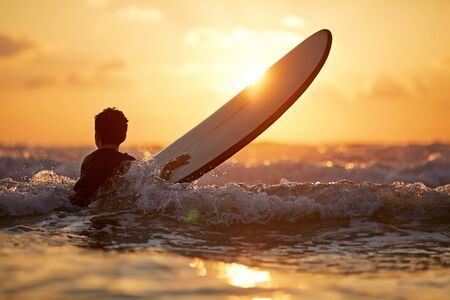 Confident boy carrying surfboard while standing at seaside in sunset Stockfoto