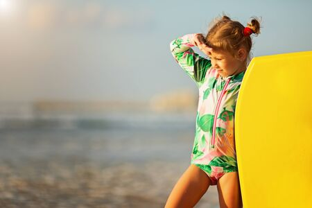 Summer Travel Beach Vacation. Beautiful little girl in a swimsuit With Surfboard