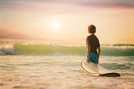 Back view of the little surfer boy surfing lifestyle relaxing holding surfboard looking at ocean waves for surf