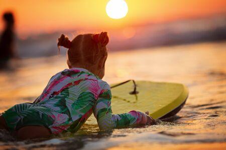 Waves splashing near girl with surfboard on sunset on an autumn day