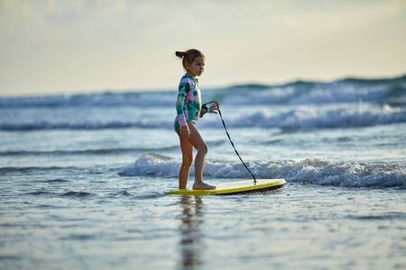 little girl in a bright colorful swimsuit with a bodyboard A child trying to ride bodyboard