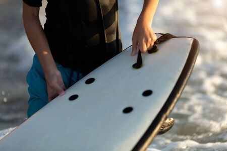 Close up detail of little boy holding surfboard on beach at waters edge on active summer vacation.