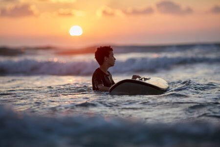 Surfer waiting in the line up for a wave at sunrise or sunset Stockfoto