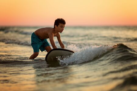 Side view of fearless kid floating surfboard at ocean with waves on sunny evening
