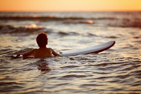 Young Man Riding Wave at Sunset. Outdoor Active Lifestyle. Surfing at Sunset