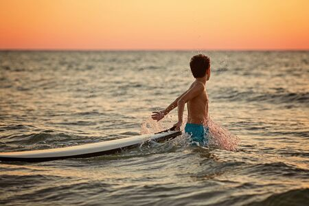 Happy little surfer boy makes splashes with hands at golden sunset