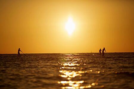 surfing under amazing dark sunset sky with three people. Stockfoto