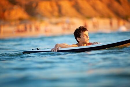 Young surfer, happy young boy in the ocean on surfboard