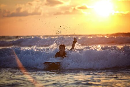 Carefree boy surfing at wave at colourful sunset