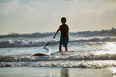 ten-year-old boy surfs at Israel Beach in Tel-Aviv. guy conquers the waves on the surfboard
