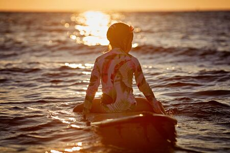 Holiday on the beach. Relaxed little girl sitting on the water with surfboard enjoying the sunset