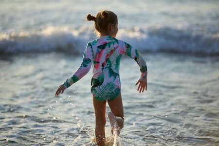 little girl having fun in the waves of the sea and the drops of water are splashing all over her Stockfoto