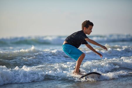 little boy surfing on a surfboard in the indian ocean.