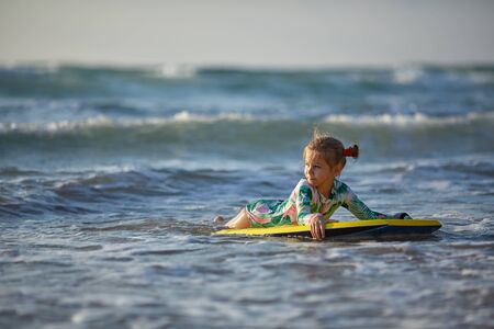 Little baby girl young surfer with bodyboard has a fun on small ocean waves. Active family lifestyle